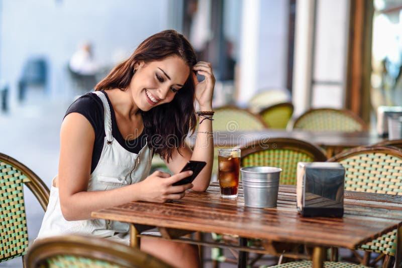 Le kvinnan med blåa ögon som sitter på det stads- kafét genom att använda den smarta telefonen royaltyfria bilder
