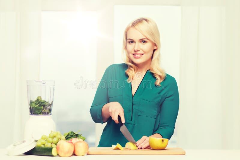 Le kvinnan med blandarematlagningmat hemma arkivfoto