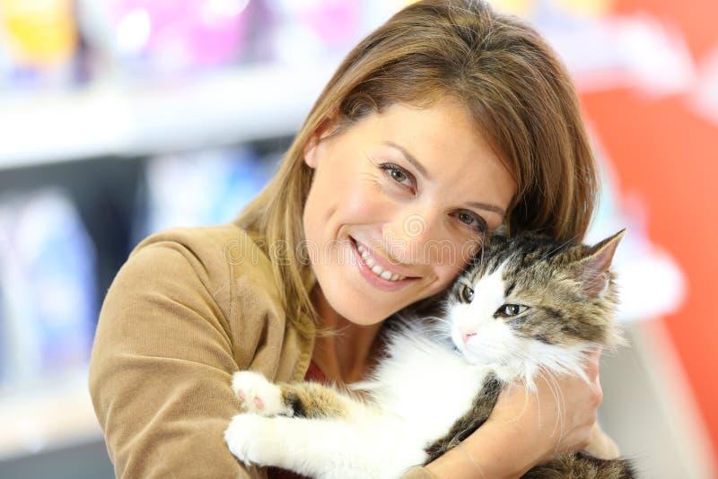 Le kvinnan med den gulliga lilla katten royaltyfria bilder