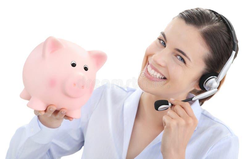 Le kvinnan med den isolerade hörlurar med mikrofon och spargrisen på vitbaksida royaltyfri bild