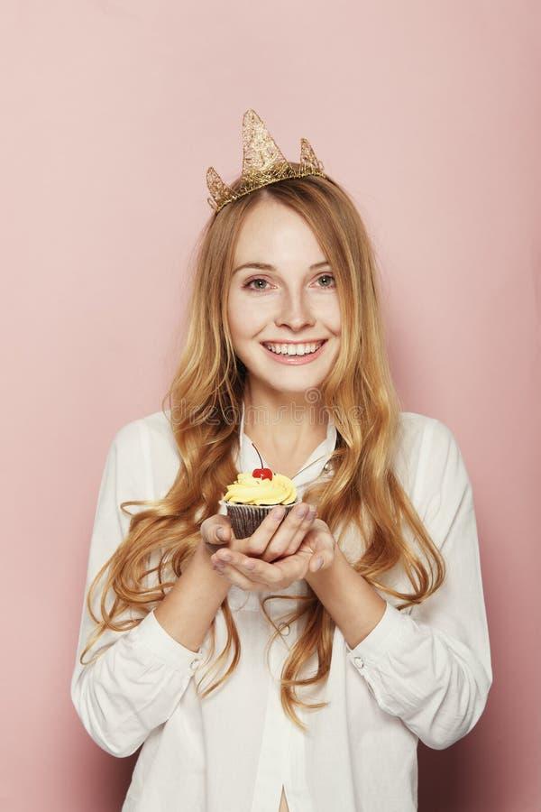 Le kvinnan, med en krona som rymmer en födelsedagmuffin arkivfoto