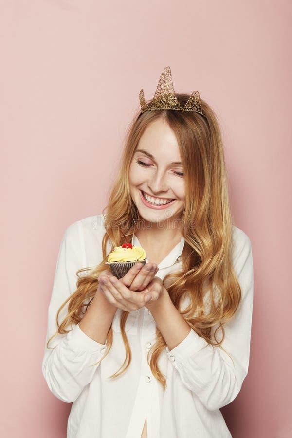 Le kvinnan, med en krona som rymmer en födelsedagmuffin arkivbild