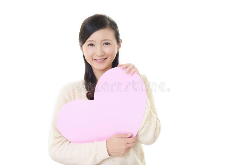 Le kvinnan med en rosa hj?rta royaltyfri fotografi