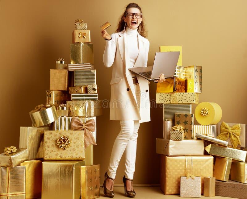 Le kvinnan med guld- bärbar dator- och kreditkortfröjd arkivbilder