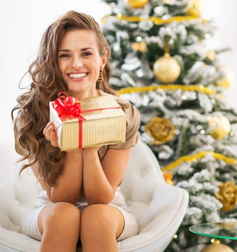 Le kvinnan med julgåva boxas nära julträd royaltyfria foton