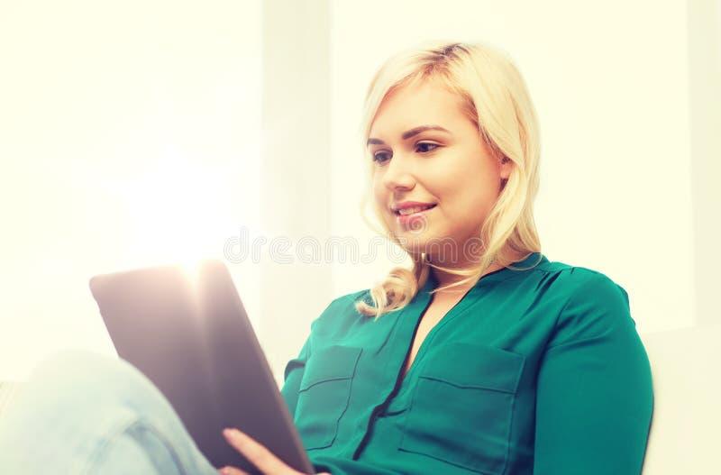 Le kvinnan med minnestavlaPC hemma fotografering för bildbyråer