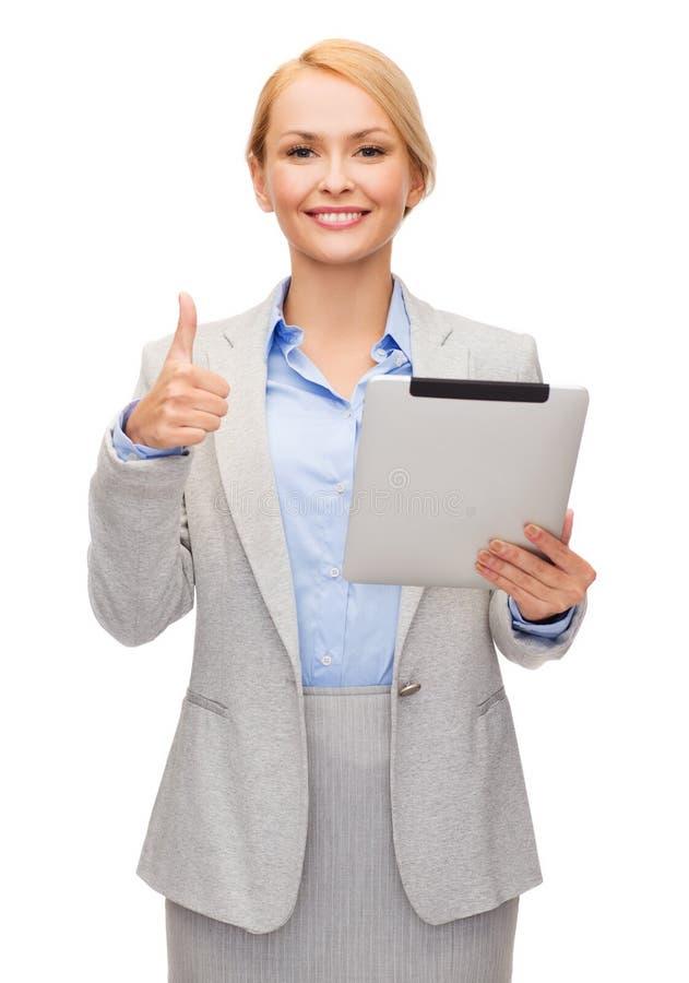 Le kvinnan med minnestavlaPC:n som visar upp tummar arkivfoto