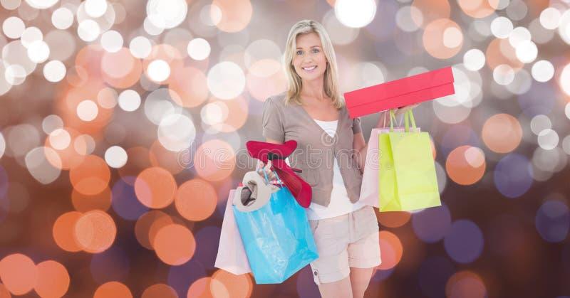 Le kvinnan med shoppingpåsar och askar över bokeh royaltyfri foto