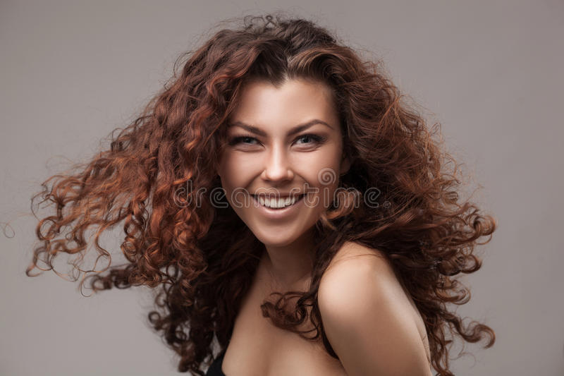 Le kvinnan med sunt brunt lockigt hår arkivbild