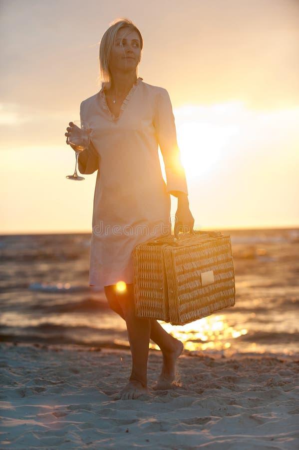 Le kvinnan med vinexponeringsglas på stranden på solnedgången arkivfoton