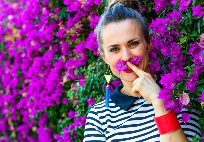 Le kvinnan nära färgrik magentafärgad blommasäng som har rolig tid royaltyfri fotografi