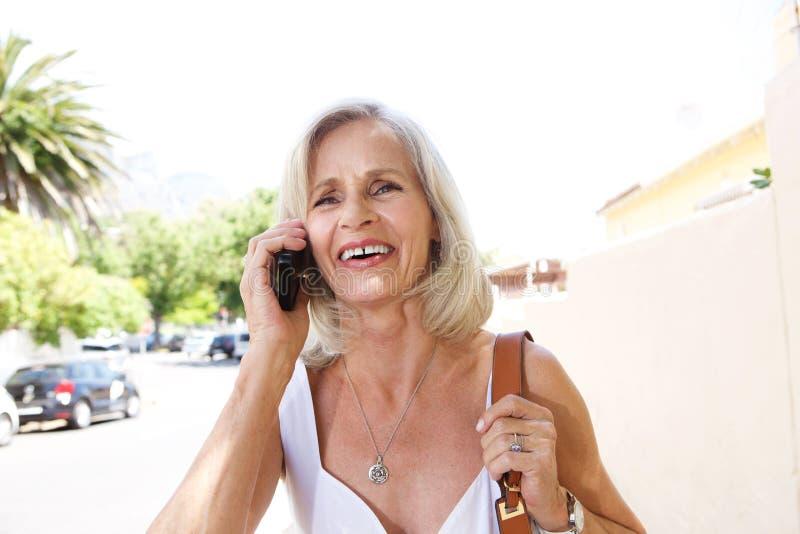 Le kvinnan på telefonen utanför på trottoaren fotografering för bildbyråer