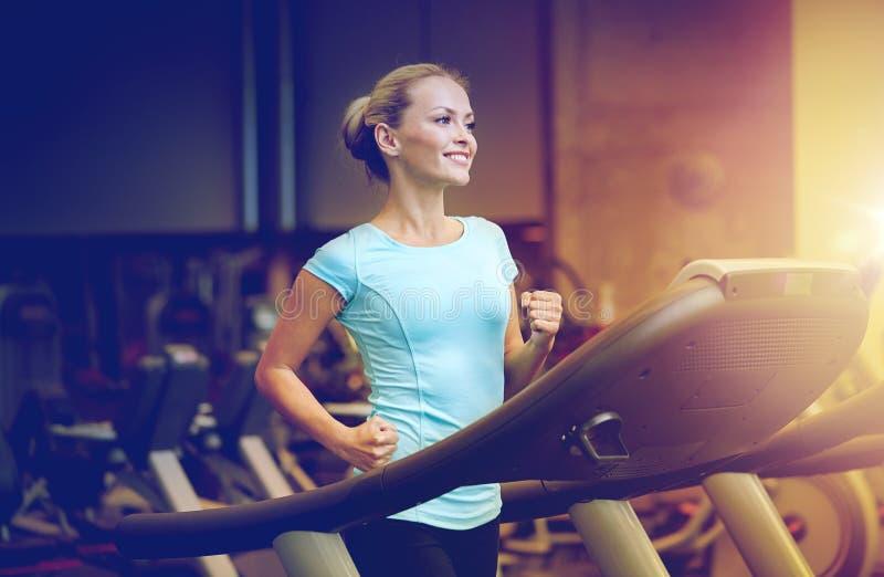 Le kvinnan som övar på trampkvarnen i idrottshall royaltyfri fotografi