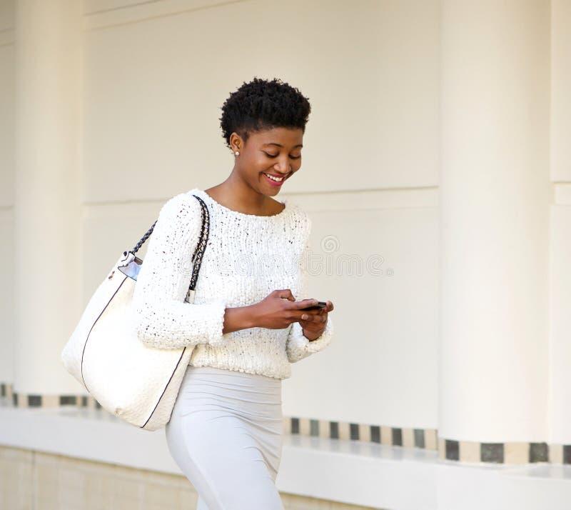 Le kvinnan som överför textmeddelandet på mobiltelefonen royaltyfri bild