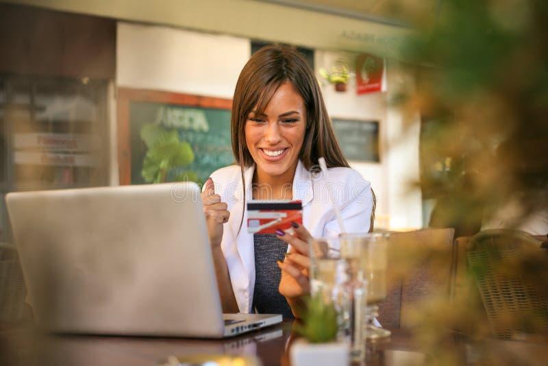 Le kvinnan som använder bärbara datorn för att kontrollera kreditkorten arkivfoto