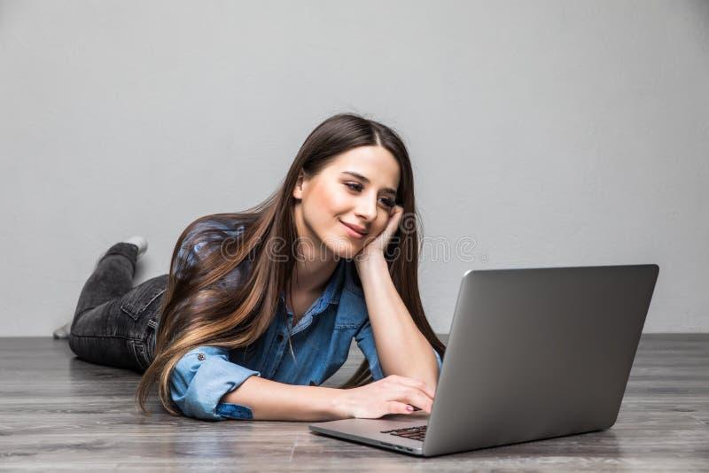 Le kvinnan som arbetar på bärbara datorn på golv arkivbilder