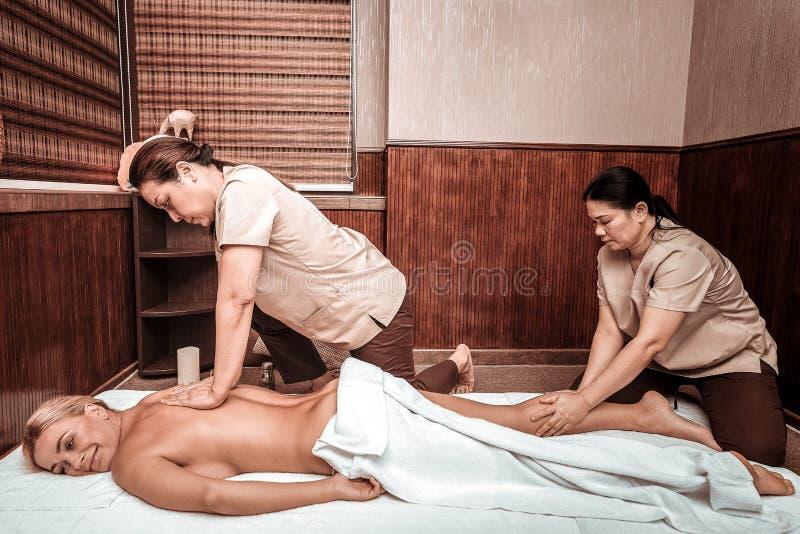 Le kvinnan som får special fyra-hand thai massage arkivfoto