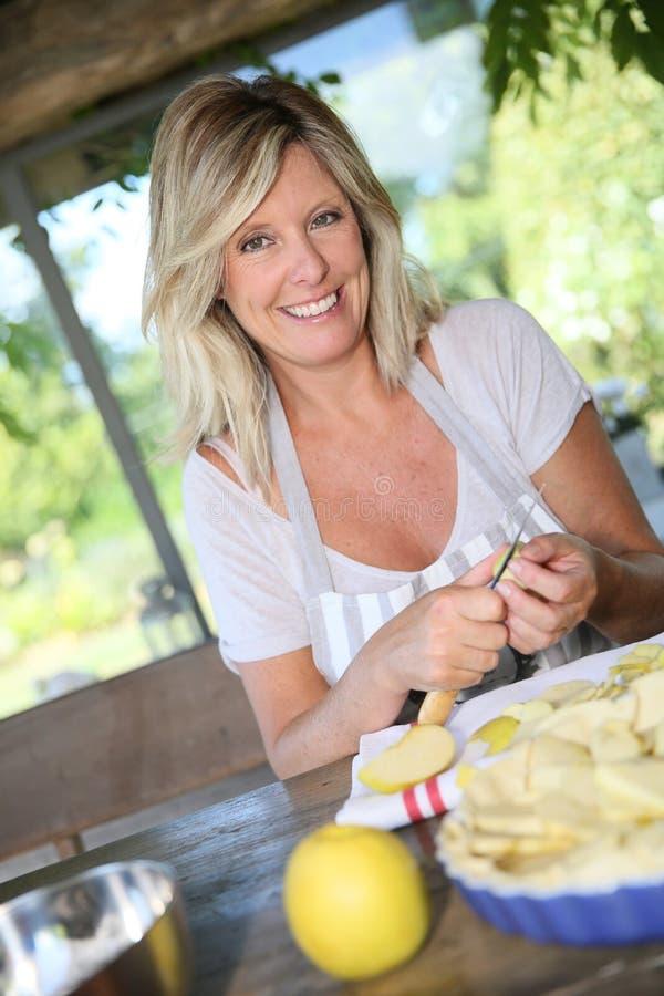 Le kvinnan som förbereder en äppelpaj royaltyfri bild