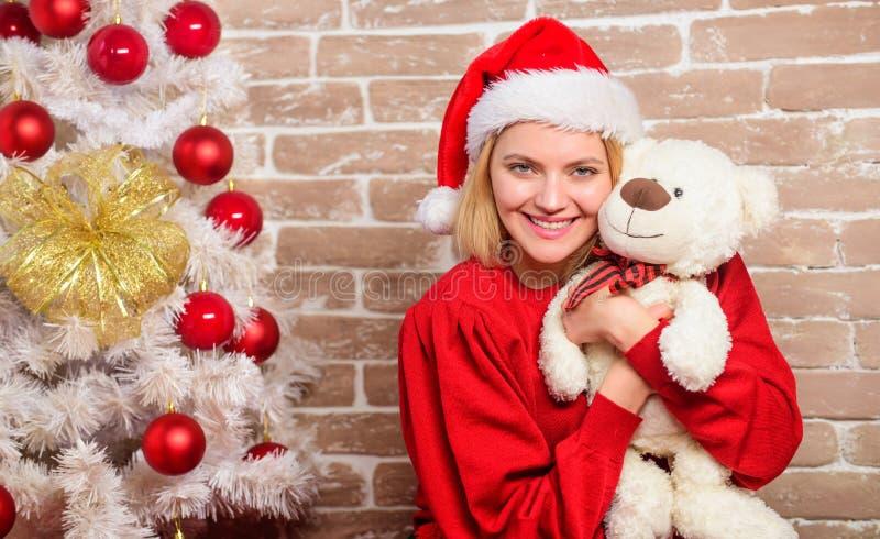 Le kvinnan som firar jul Lycklig flicka i den Santa Claus hatten Leveransjulgåvor Parti för nytt år glatt arkivbild