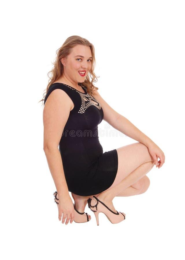 Le kvinnan som huka sig ned på golv royaltyfria foton