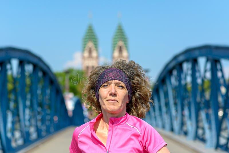 Le kvinnan som joggar över en stads- bro arkivbilder
