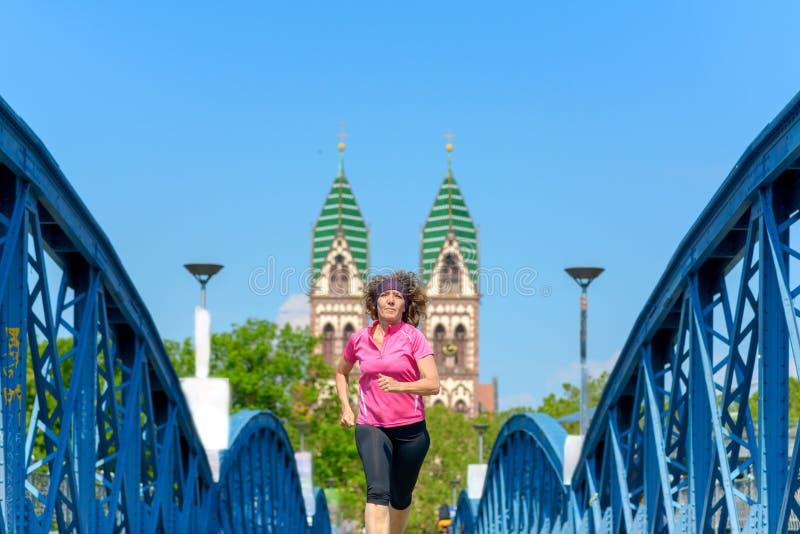 Le kvinnan som joggar över en stads- bro royaltyfri bild