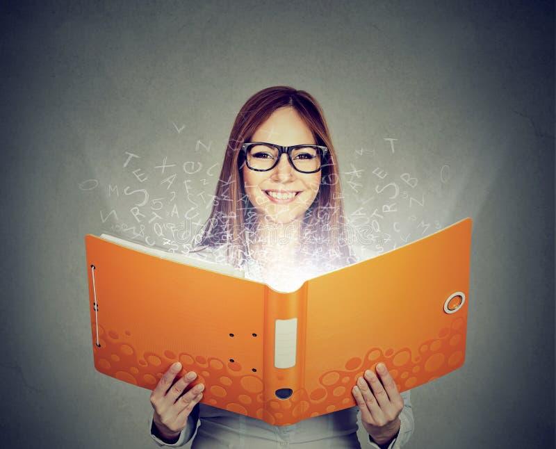 Le kvinnan som läser en bok med bokstäver som bort flyger royaltyfri foto