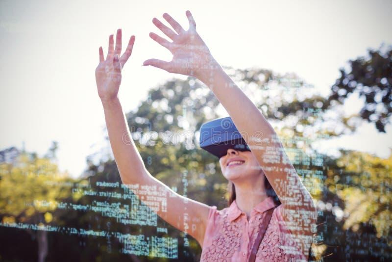Le kvinnan som lyfter henne händer, medan genom att använda en hörlurar med mikrofon för VR 3d i parkera royaltyfri bild