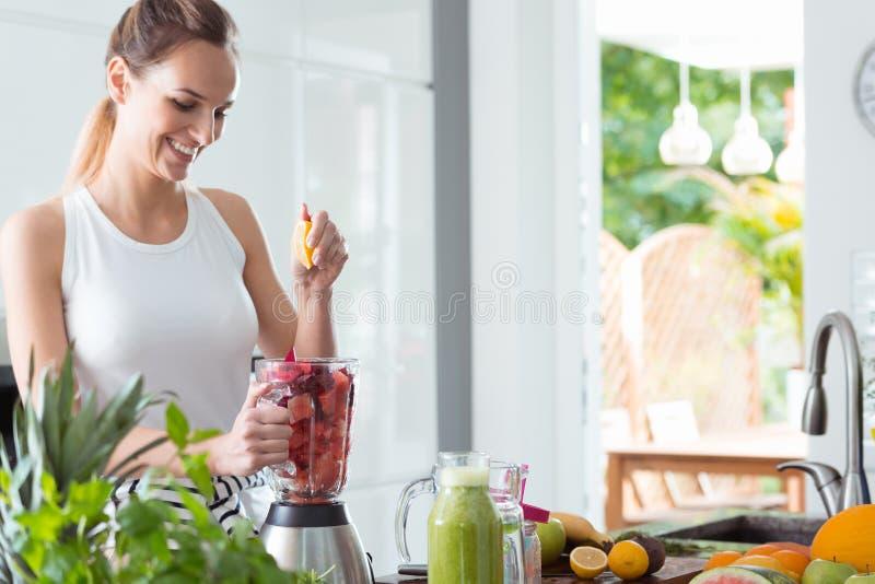 Le kvinnan som pressar orange fruktsaft royaltyfri fotografi