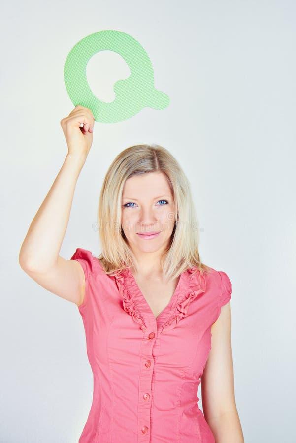 Le kvinnan som rymmer bokstaven Q royaltyfria bilder