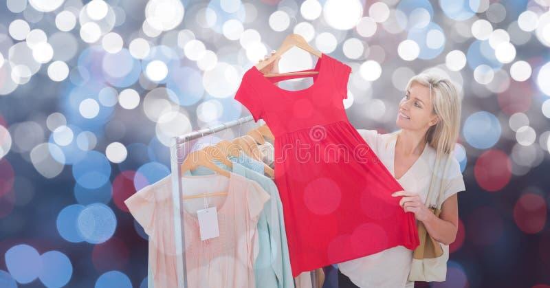 Le kvinnan som rymmer den röda klänningen över bokeh arkivfoton