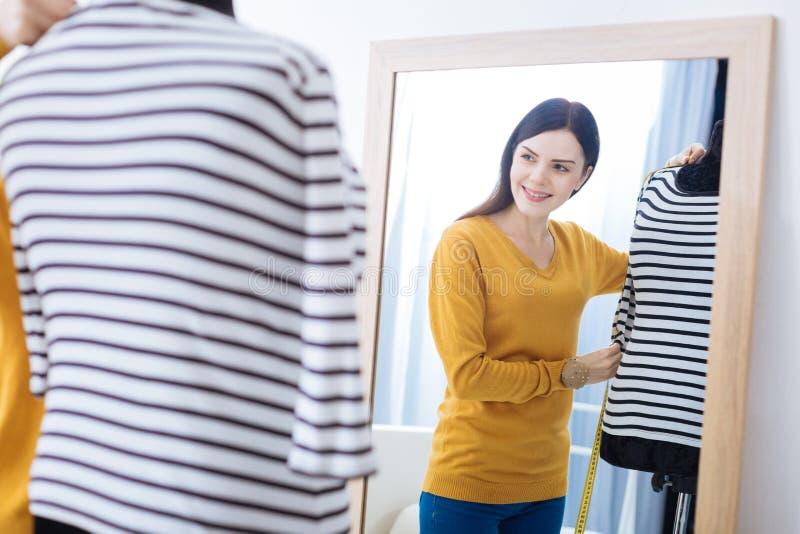 Le kvinnan som rymmer en muff och att se dess längd i spegeln fotografering för bildbyråer