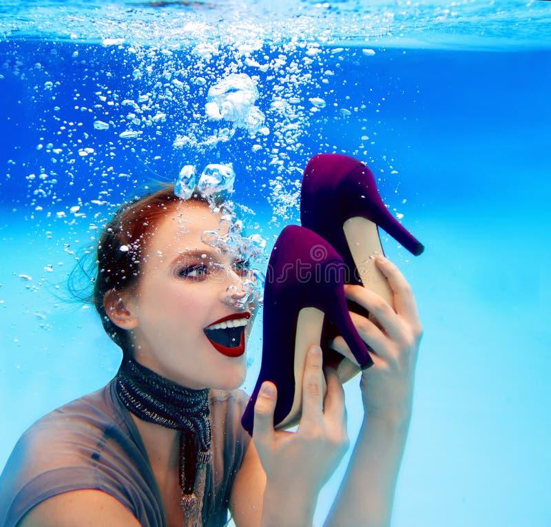 le kvinnan som rymmer ett par av skor undervattens- i simbassängen royaltyfri bild