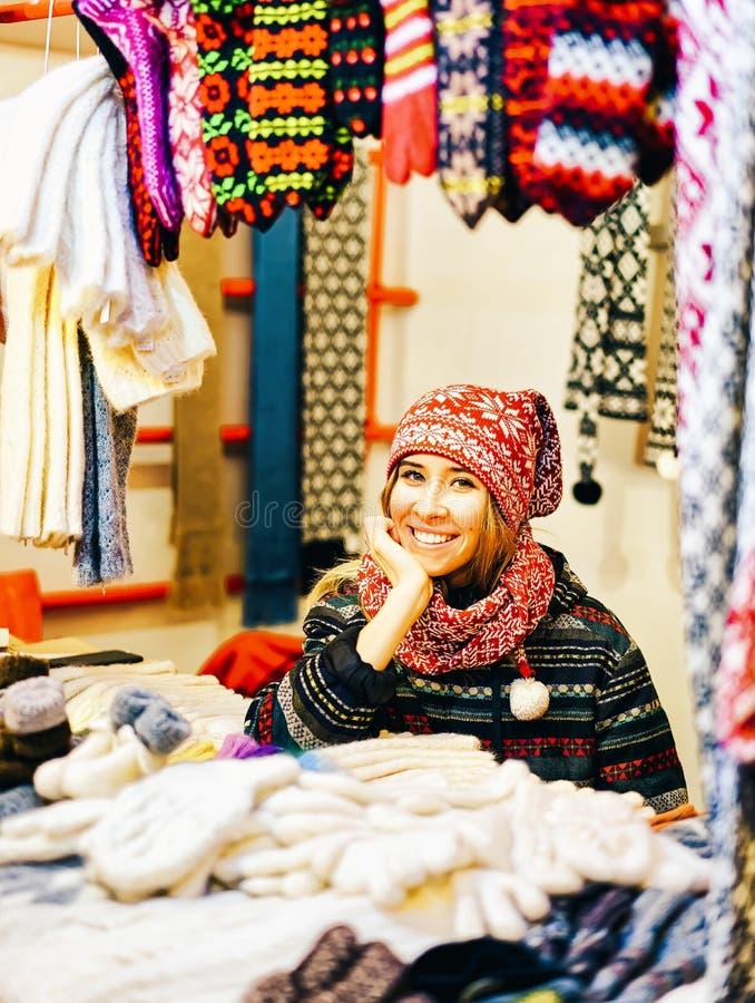 Le kvinnan som säljer varma kläder och souvenir på julmarknaden i vintern Riga i Lettland royaltyfria foton
