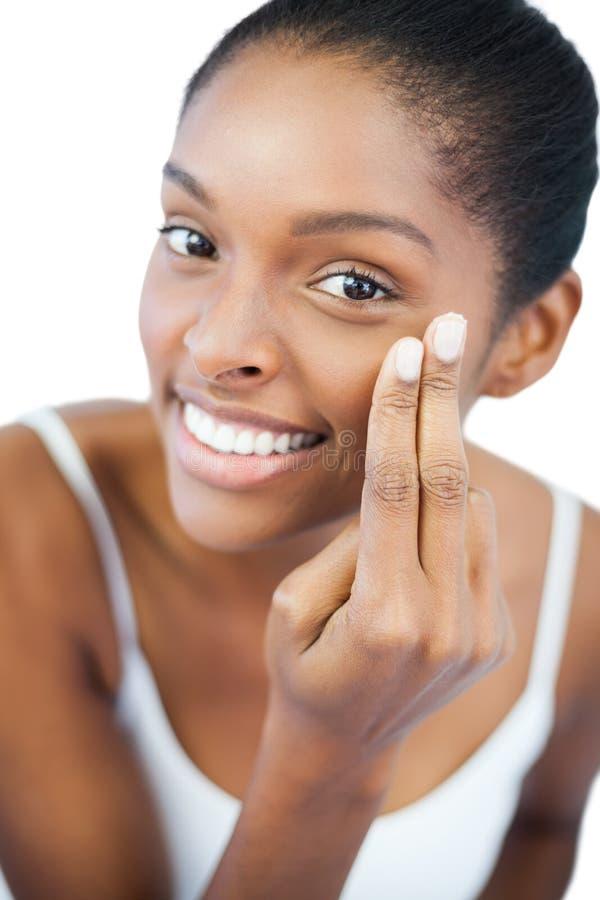 Le kvinnan som sätter fuktighetsbevarande hudkräm på hennes framsida royaltyfri foto