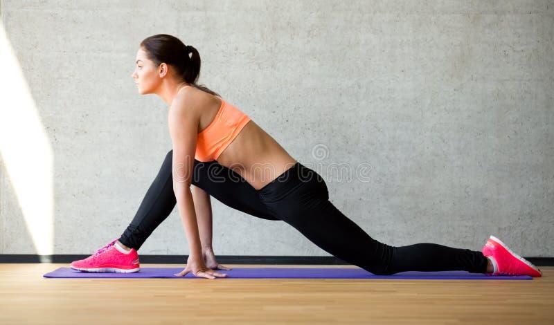Le kvinnan som sträcker benet på mattt i idrottshall royaltyfria foton