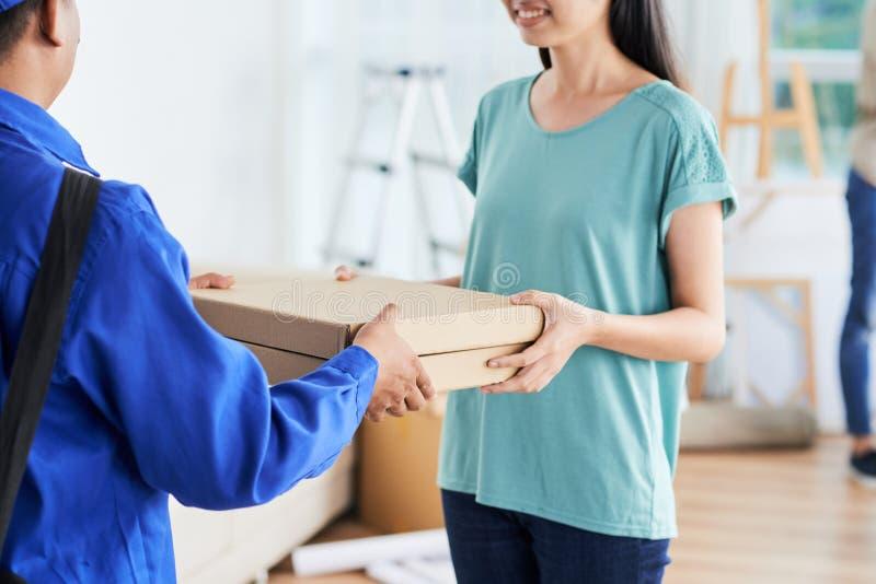 Le kvinnan som tar pizza från kurir royaltyfri bild