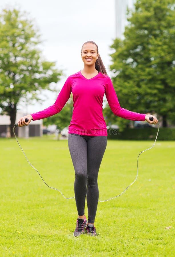Le kvinnan som utomhus övar med hopp-repet arkivfoton
