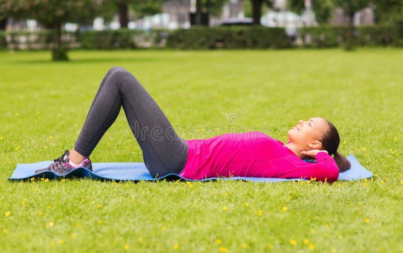 Le kvinnan som utomhus gör övningar på mattt arkivbild