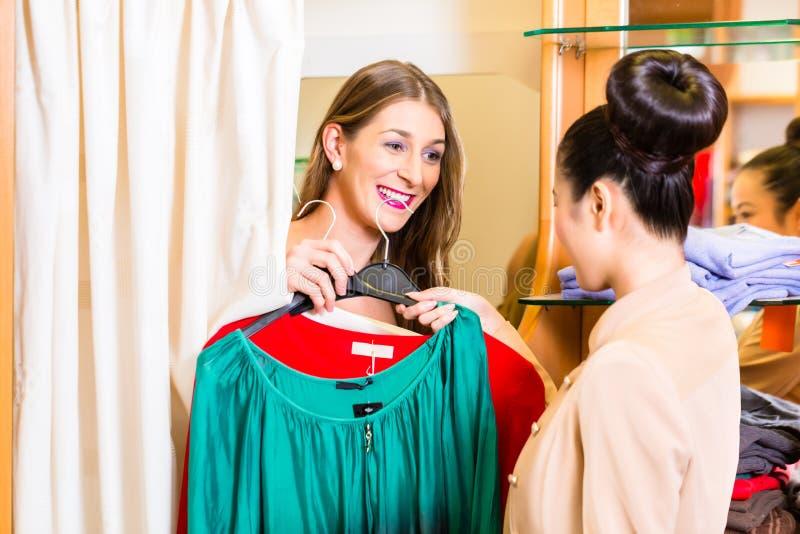 Le kvinnan som väljer kläder för att köpa arkivfoton