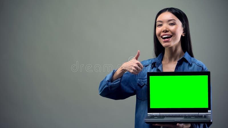 Le kvinnan som visar tummarsom rymmer den gr?na sk?rmb?rbara datorn, online-utbildning royaltyfri fotografi