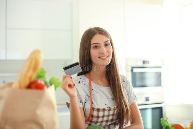 Le kvinnaonline-shopping genom att använda datoren och kreditkorten i kök royaltyfri bild
