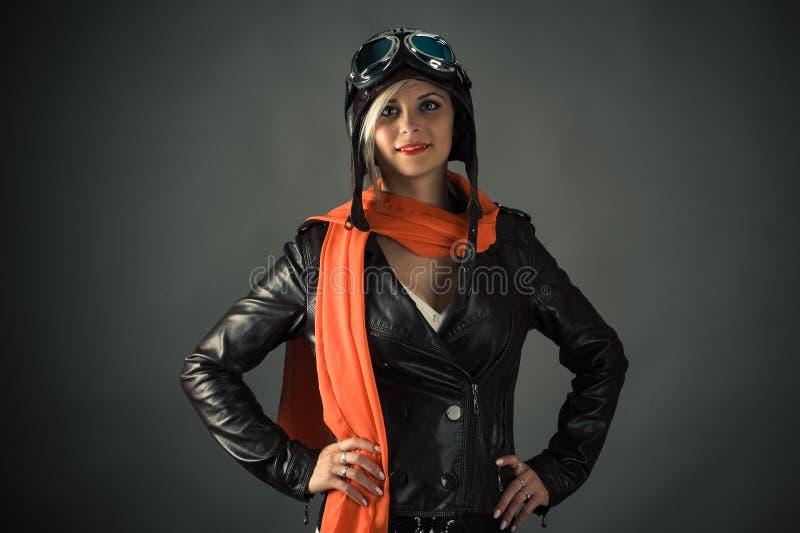 Le kvinnapiloten i röd halsduk i flygarehjälm fotografering för bildbyråer