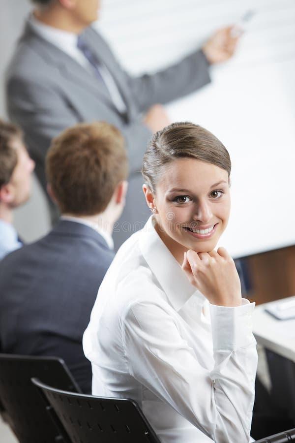 Le kvinnasammanträde på ett affärsmöte med kollegor arkivfoto