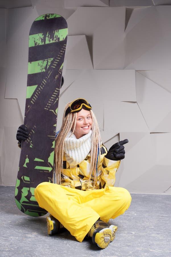 Le kvinnasammanträde på golv med snowboarden fotografering för bildbyråer