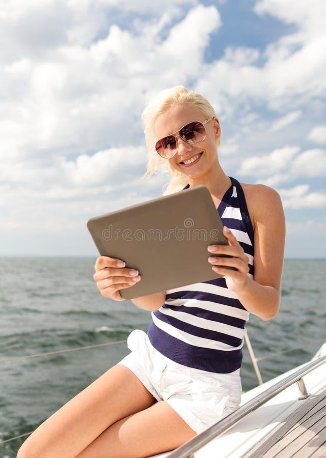 Le kvinnasammanträde på yachten med minnestavlaPC royaltyfria bilder