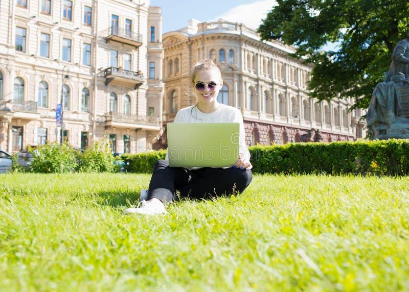 Le kvinnastudenten som söker information i internet via netto-boken arkivbild
