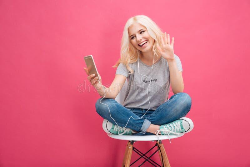 Le kvinnavideoen som pratar på smartphonen arkivfoto