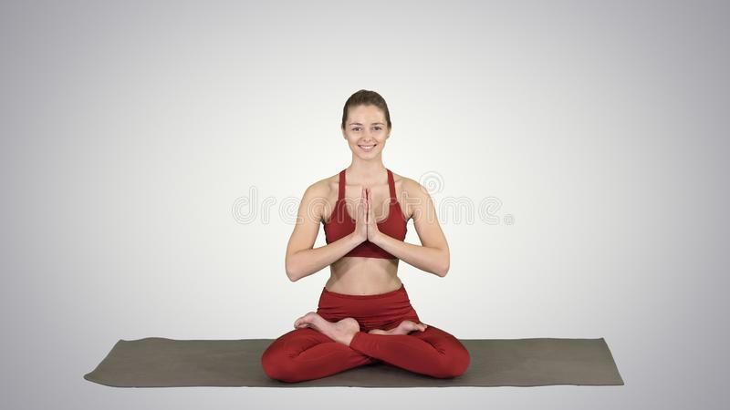 Le kvinnayoga som mediterar sittande lotusblomma, h?nder som kopplas ihop p? lutningbakgrund royaltyfri bild