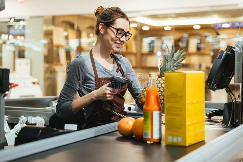 Le kvinnliga objekt för kassörskascanninglivsmedelsbutik arkivbilder